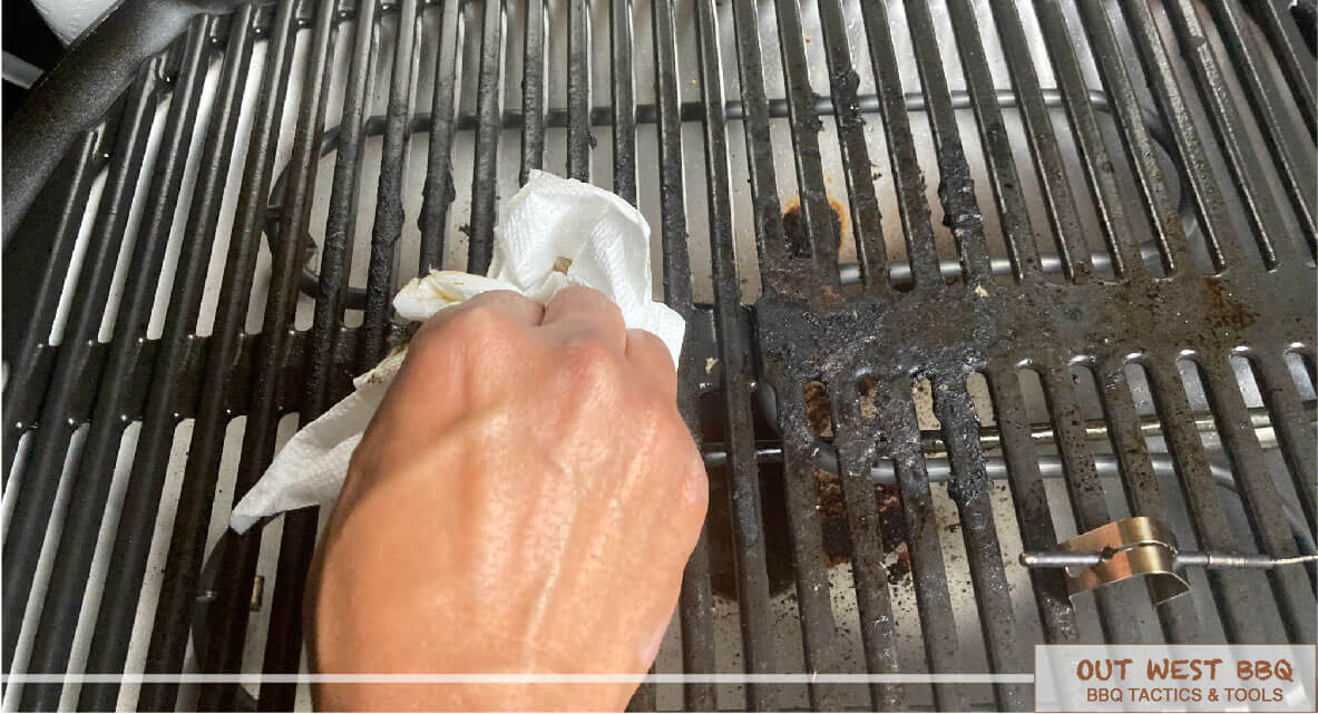 man cleaning electric grill grate with cloth